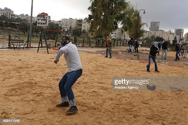 Palestinian man uses a slingshot to hurl stones towards Israeli soldiers during the clashes following a protest against Israeli violations at alAqsa...