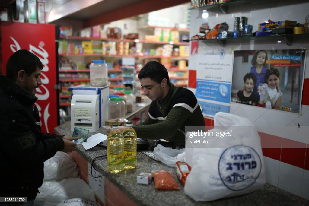 A Palestinian man uses her World Food Programme ration card in a