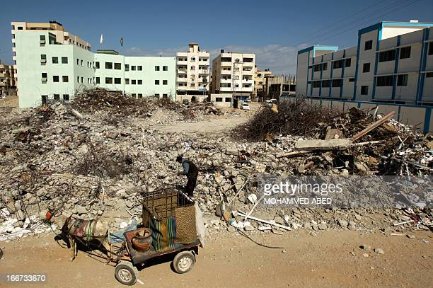 Palestinian man uses his donkey cart to collect scrap metal from the ruins of the ministry of interior building in Gaza City which was destroyed...