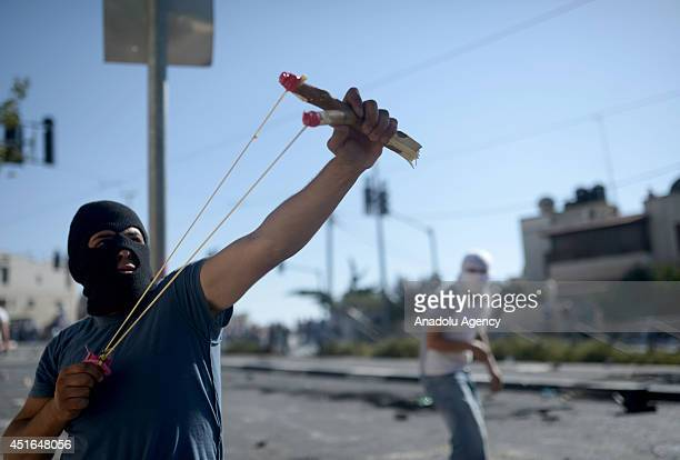Palestinian man uses slingshot tu hurl stones at Israeli security forces during the clashes over the abduction and killing of a Palestinian teen by...