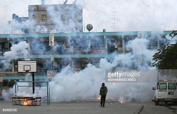 A Palestinian man walk away from heavy smoke following an Israeli strike over a UN school in Beit Lahia northern Gaza Strip early on January 17 2009...
