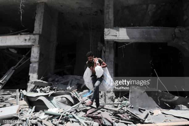 Palestinian man walks at the rubble of the severely damaged Al-Jawhara Tower in Gaza City on May 12, 2021 after it was hit by Israeli airstrikes amid...