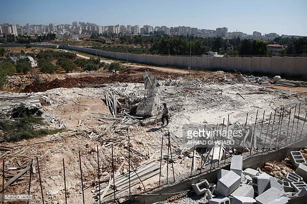 A Palestinian man walks atop the rubble of a house that was demolished by Israeli army bulldozers in the village of Qalandia next to Israel's...