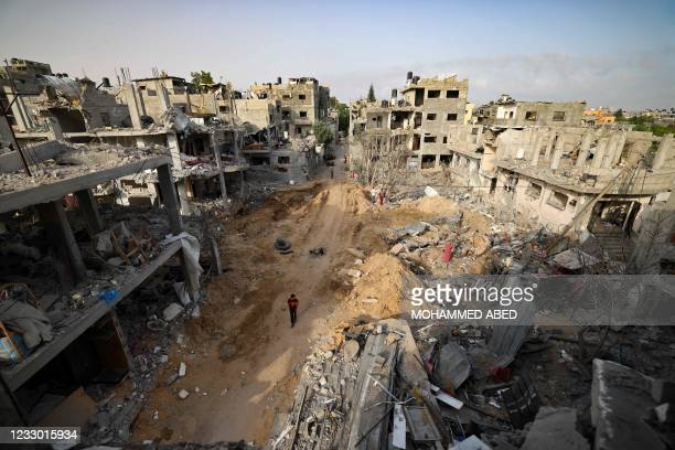 Palestinian man walks in a neighbourhood hit by Israeli bombardment in Gaza City, after a ceasefire brokered by Egypt between Israel and Hamas, on...
