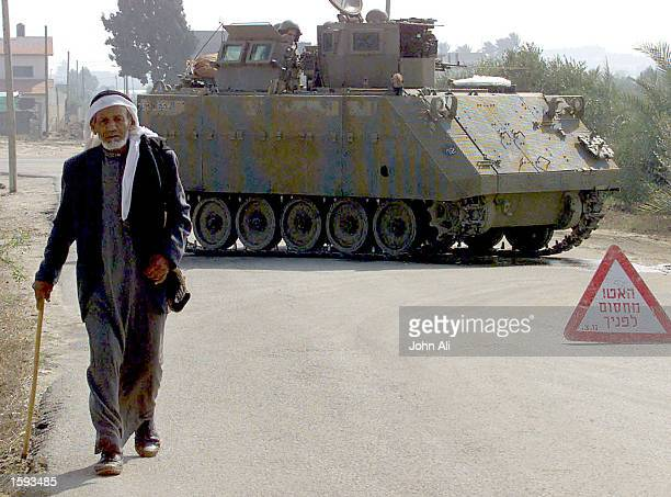 Palestinian man walks in front of Israeli tanks carrying Israeli soldiers who closed the road November 23 2000 between South and North Gaza Strip...