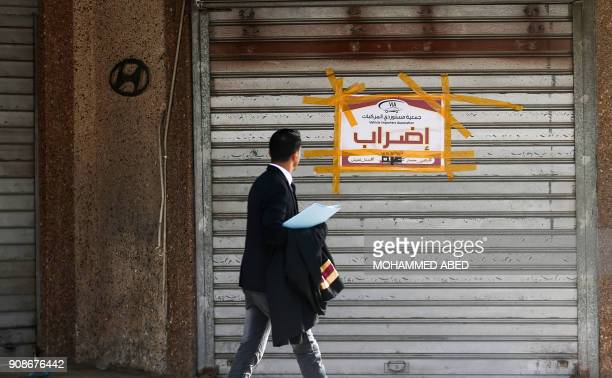 Palestinian man walks in Gaza City past a poster hung on a shop reading in Arabic 'strike' in protest against the siege on Gaza and the economic...