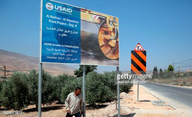 A Palestinian man walks near a USAID billboard in the village of alBadhan north of Nablus in the occupied West Bank on August 25 2018 Since January...