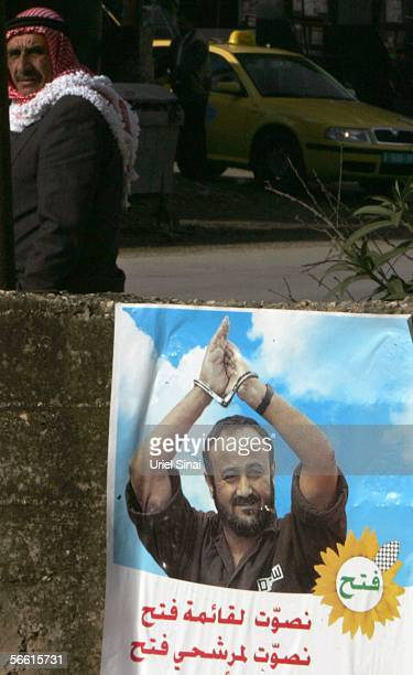 A Palestinian man walks past a campaign poster of jailed Fatah leaded Marwan Barghuti January 18 2006 in the West Bank village of Chawara The...