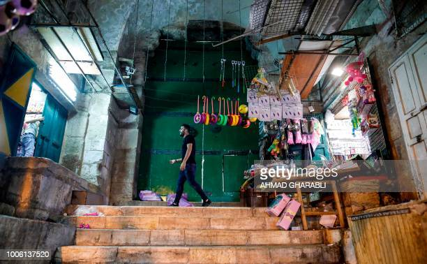 A Palestinian man walks past a closeddown gateway that leads to the Aqsa mosque compound in the Old City of Jerusalem on July 27 after the site was...
