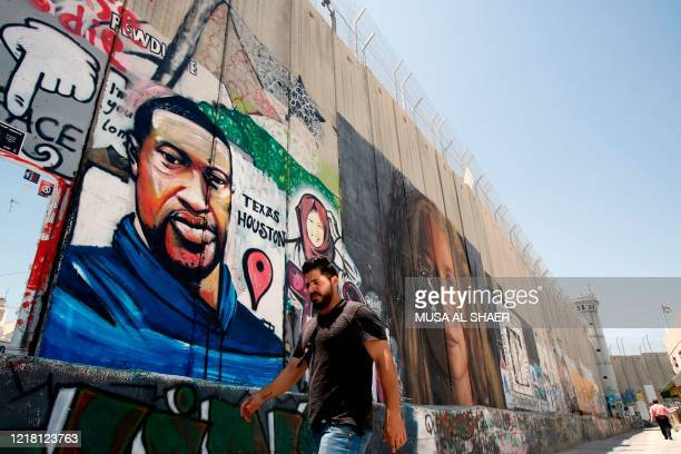 Palestinian man walks past a graffiti of George Floyd an unarmed black man who died after a white policeman knelt on his neck during an arrest in the...