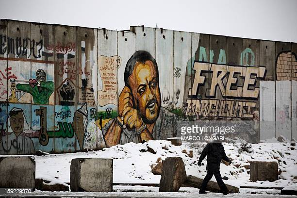 A Palestinian man walks past a graffiticovered section of the controversial Israeli separation wall at the Qalandia checkpoint in the Israeli...