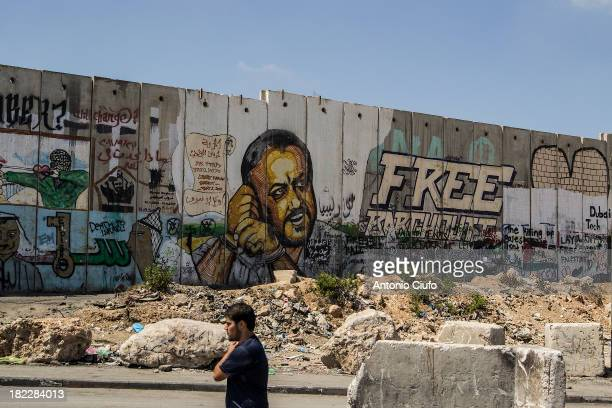 Palestinian man walks past a mural of Fatah leader Marwan Barghouti at Qalandiya refugee camp. Marwan Hasib Ibrahim Barghouti is a Palestinian...