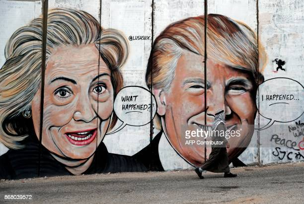 Palestinian man walks past a newly sprayed graffiti depicting US presidential candidate Hillary Clinton and US President Donald Trump on the...
