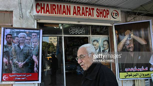 A Palestinian man walks past a shop in Gaza City displaying posters of Fatah leader Marwan Barghuti and Popular Front for the Liberation of Palestine...