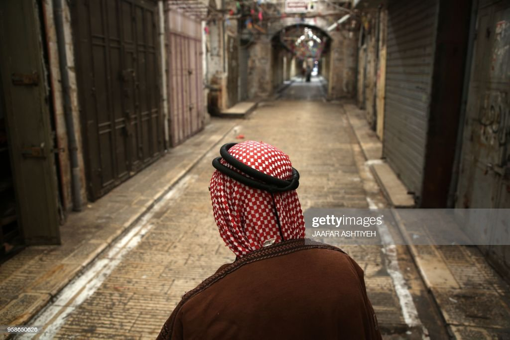 Palestinian man walks past closed shops on an empty street in the Israeli occupied West Bank city of Nablus on May 15, 2018, during a general strike called for by leaders in solidarity with Gaza and in protest against the US embassy's move to Jerusalem.