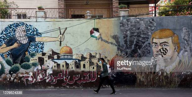 Palestinian man walks past graffiti depicting outgoing US President Donald Trump with a footprint painted on his face, drawn on a wall along a street...
