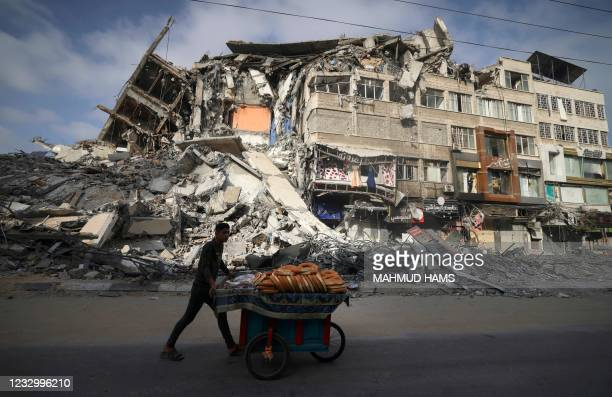 Palestinian man walks past the destroyed Al-Shuruq building in Gaza City on May 20, 2021 after it was bombed by an Israeli air strike. - Israel and...