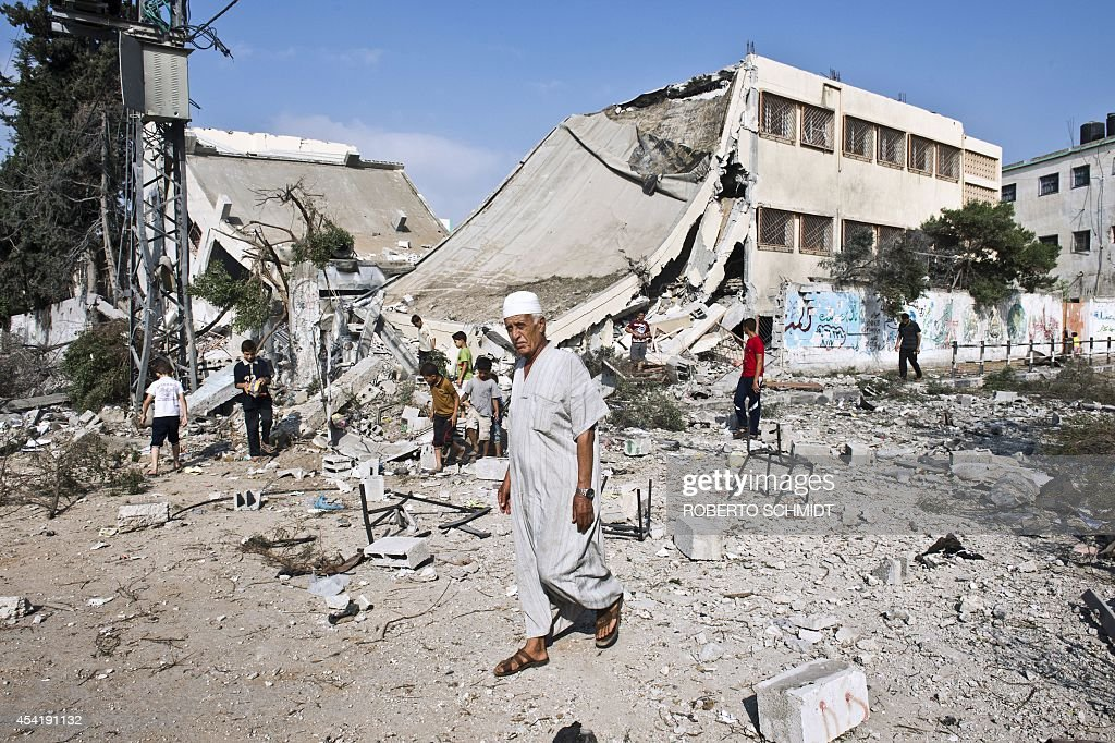 A Palestinian man walks past the toppled remains of a government school that was targeted by overnight Israeli air strikes on Gaza City on August 26, 2014. Israeli air raids on Gaza City killed two Palestinians while scores more were wounded when warplanes bombed two high-rise residential blocks, medics and witnesses said. The raids came as Israel stepped up the pressure on Hamas on day 50 of a bloody confrontation which began on July 8 and has claimed the lives of more than 2,100 Palestinians and 68 on the Israeli side.