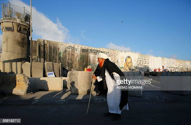 Palestinian man walks towards the Qalandia checkpoint a main crossing point between the West Bank city of Ramallah and Jerusalem on June 10 as they...