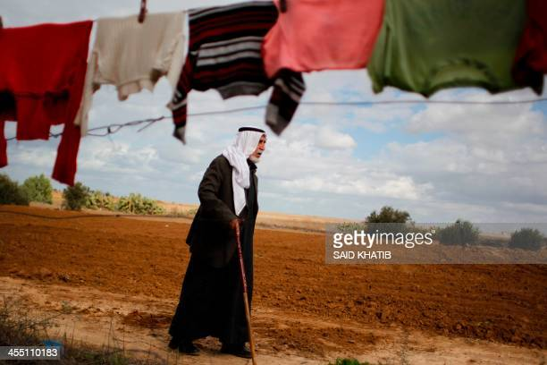 Palestinian man walks under a line of hanging laundry in Absan near the border between Israel and east of the town of Khan Yunis in the southern Gaza...