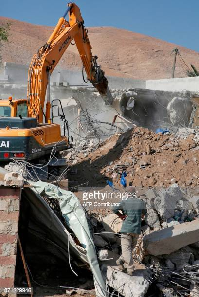 A Palestinian man watches as an Israeli army bulldozer demolishes a Palestinian house that was reportedly built without permission in the West Bank...