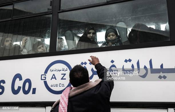 Palestinian man waves to his family on a bus before they cross into Egypt through the Rafah border crossing after it was opened by Egyptian...