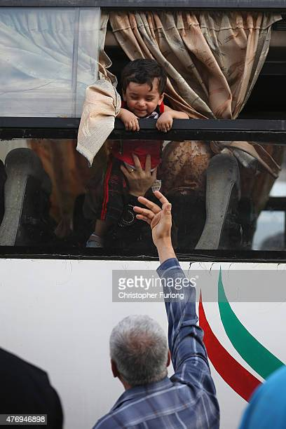 Palestinian man waves to relatives onboard a bus crossing the border into Egypt at the southern Gaza Rafah Crossing on June 13 2015 in Rafah Gaza The...