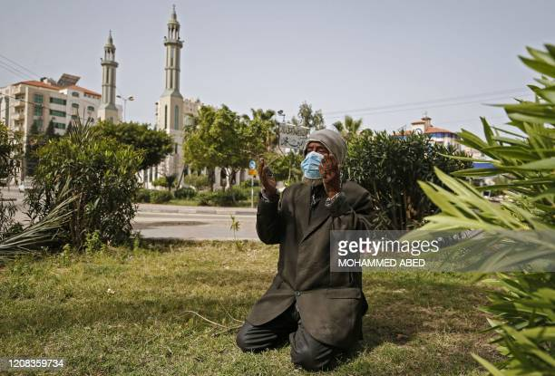 Palestinian man wearing a mask prays outside a closed mosque in Gaza City after it was closed as a measure to contain the spread of the COVID-19...