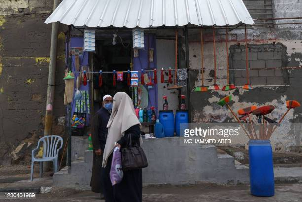 Palestinian man wearing a protective mask amid the COVID-19 pandemic stands by a shop he opened at home, at the al-Shati camp for Palestinian...