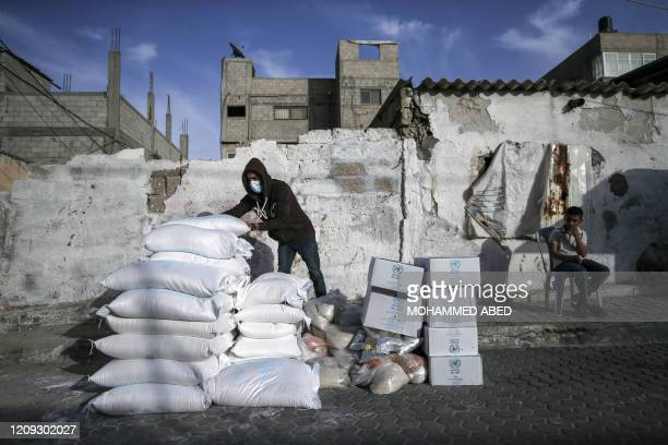Palestinian man wearing a protective mask sorts food aid provided by the United Nations Relief and Works Agency for Palestinian Refugees , to be...
