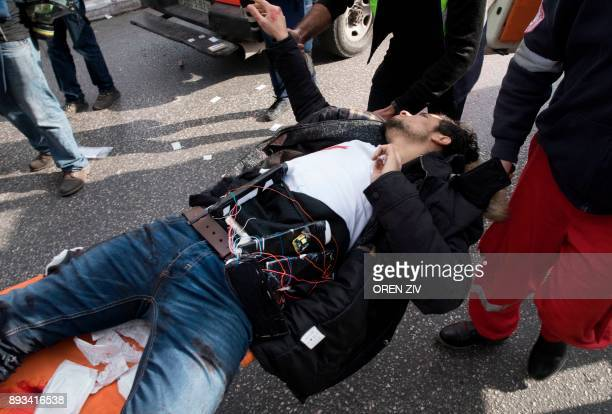 A Palestinian man wearing a suspected suicide vest is carried into an ambulance after he was shot by Israeli forces for stabbing a soldier in the...