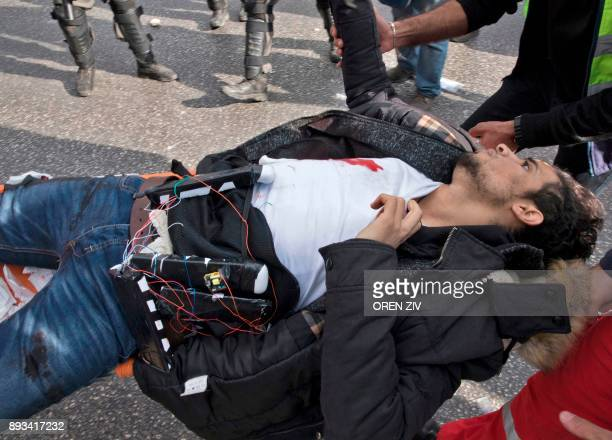 Palestinian man wearing a suspected suicide vest is carried into an ambulance after he was shot by Israeli forces for stabbing a soldier in the...