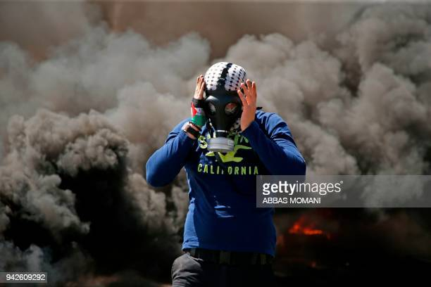 Palestinian man wears a gas mask next to burning tyres during a protest in the West Bank city of Ramallah on April 6 2018 Clashes erupted on the...