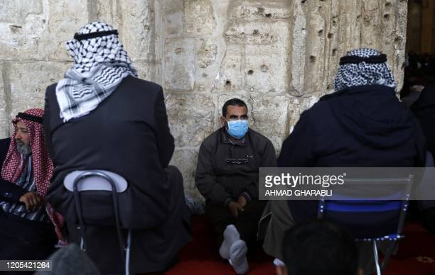 A Palestinian man wears a protective mask as a means of prevention against the coronavirus COVID19 ahead of the Friday prayers nside the alAqsa...