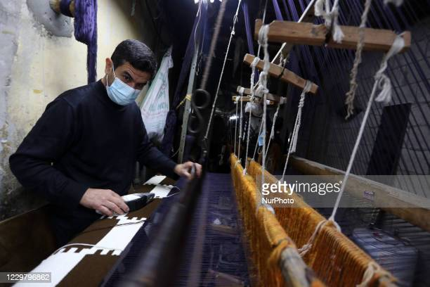 A Palestinian man weaves a carpet on a loom at a workshop amid the coronavirus disease outbreak in Gaza city on November 26 2020