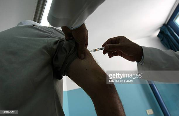 A Palestinian man who has registered to perform the annual pilgrimage to the Muslim holy places in Saudi Arabia gets a flu shot at a medical centre...