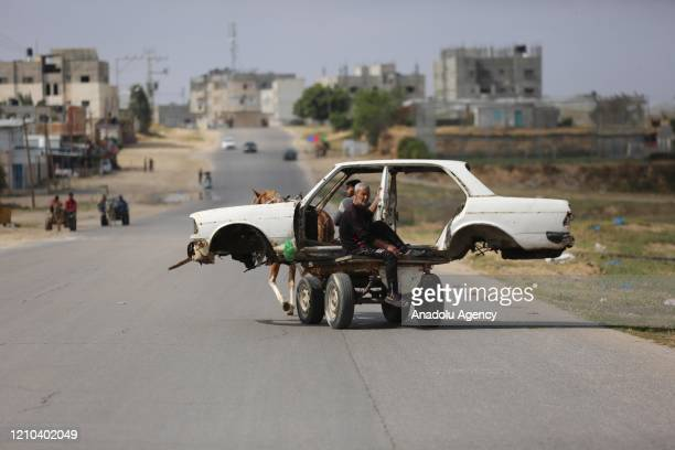 Palestinian man who makes a living by collecting scrap carries a car hood with his horse cart in Khan Yunis Gaza on April 19 2020