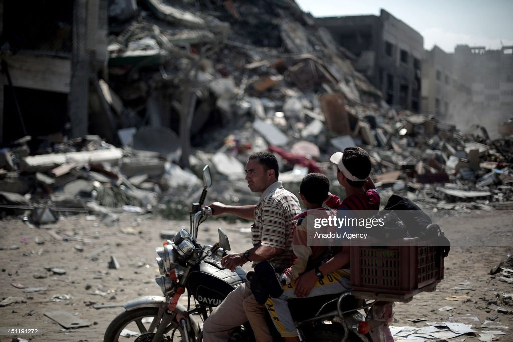 A Palestinian man with his children rides on a bike through the debris as Palestinians inspect and collect remains from the rubble of a destroyed building named Italian Tower, one of the tallest buildings in Gaza, in al-Nasr neighborhood of Gaza City, Gaza on August 26, 2014. Israeli warplanes launched attacks on the tower in al-Nasr neighborhood in Gaza City on Monday, injuring 20 Palestinians.