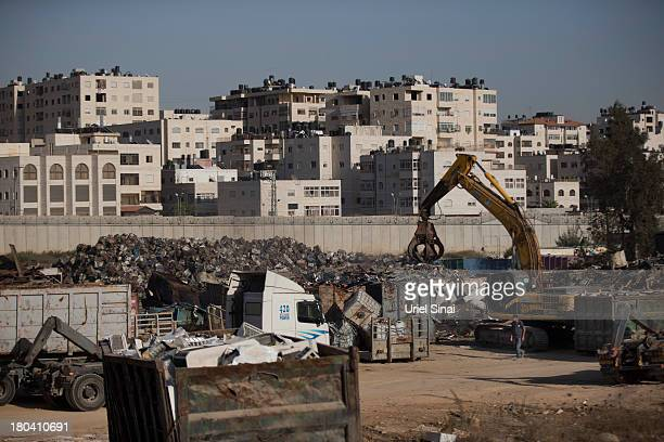 Palestinian man works in a junkyard near the Israeli West Bank barrier on the outskirts of Jerusalem on September 12 2013 in Aram West Bank The...