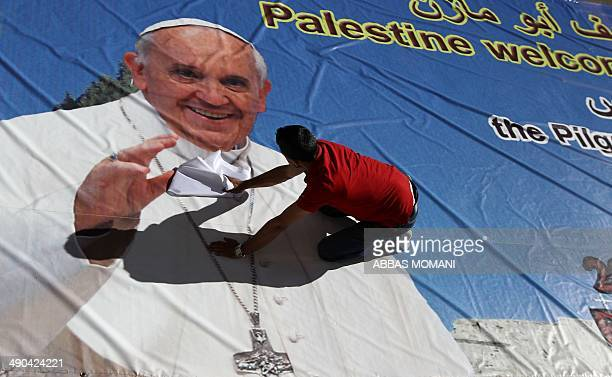 A Palestinian man works on a giant banner bearing a portrait of Pope Francis on May 14 2014 at a printing house in the West Bank city of Ramallah The...