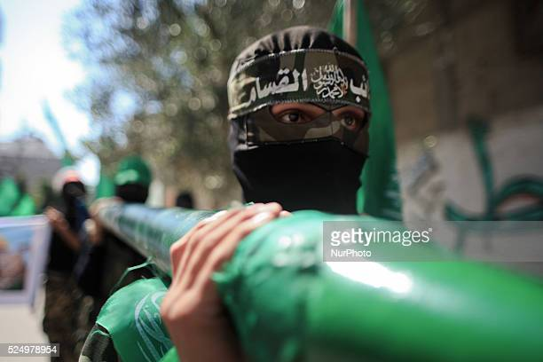 A Palestinian masked of Hamas holds Qassam rocket during a rally marking 13th anniversary of the socalled AlAqsa uprising or 'Second Intifada' and...