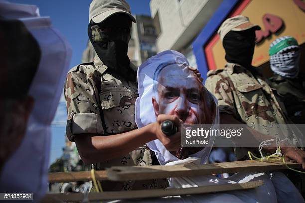 A Palestinian masked of Hamas put a dagger on head of model simulation for the President of Israeli government Shimon Peres during a rally marking...