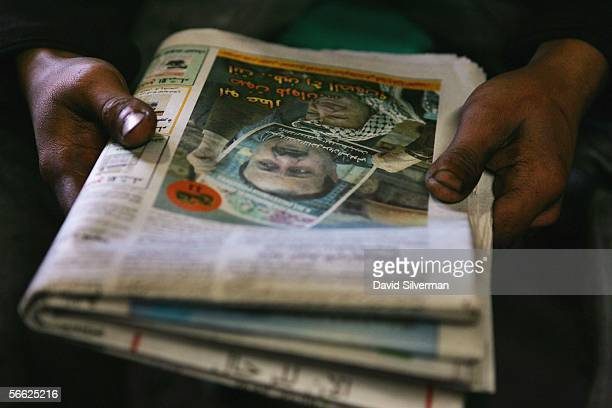 Palestinian mechanic holds the morning's Arabiclanguage newspaper as he reads a campaign advert for Palestinian leader Marwan Barghoutti who is...
