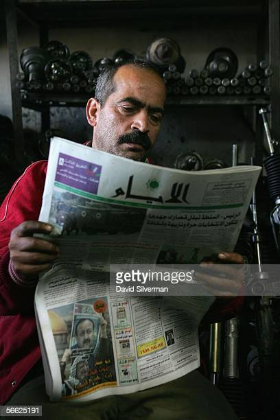 Palestinian mechanic Nidam Mahmoud Jabber reads the morning's Arabic newspaper which runs a campaign advert for Palestinian leader Marwan Barghoutti...