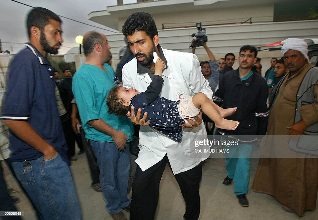 A Palestinian medic carries a wounded child into al-Najar hospital following a rocket attack by an Israeli helicopter gunship in the southern Gaza Strip refugee camp of Rafah early 20 May 2004. Five Palestinians were killed in the attack. Nineteen Palestinians has been killed in Rafah since 19 May, including 10 who died when the Israeli army opened fire on some 500 protesters marching in the Tal Al-Sultan area. AFP PHOTO/Mahmud HAMS