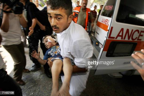 Palestinian medic carries an injured young girl into the Shifa hospital after an Israeli aircraft shelled a house in Gaza City 15 July 2006 Two...