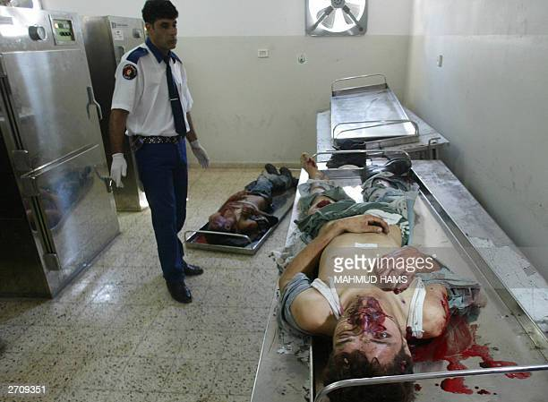Palestinian medical worker stands over the bodies of two Palestinians in the morgue of Gaza City's alShifa hospital 08 November 2003 The two men were...