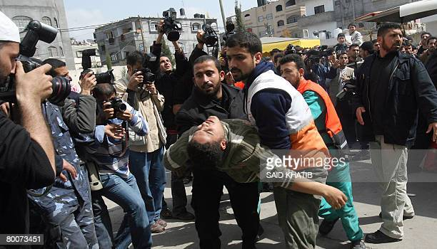 Palestinian medical workers carry a wounded man into a hospital at Beit Lahia in the northern Gaza Strip on March 1 2008 Israel pressed its assault...