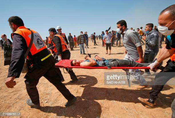 TOPSHOT Palestinian medics carry a wounded demonstrator east of Khan Yunis in the southern Gaza Strip on May 15 during a protest marking 71th...