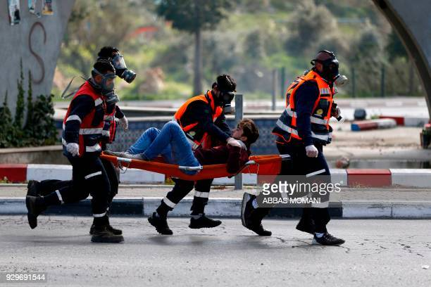 TOPSHOT Palestinian medics carry a wounded protestor during clashes following a demonstration in the West Bank city of Ramallah on March 9 2018...